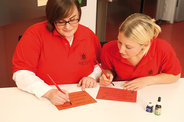 zwei frauen beschriften rote karten, foto: referat fuer bildung und sport