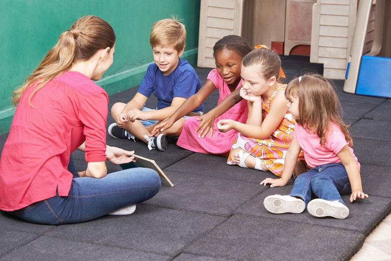 gruppe kinder redet mit erzieherin ueber buch im kindergarten, foto: fotolia, robert kneschke