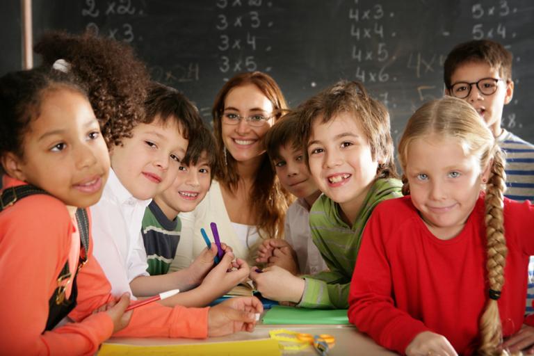 Schueler_innen mit Lehrerin laechelnd vor Tafel, Foto: iStock, Weekend Images Inc.