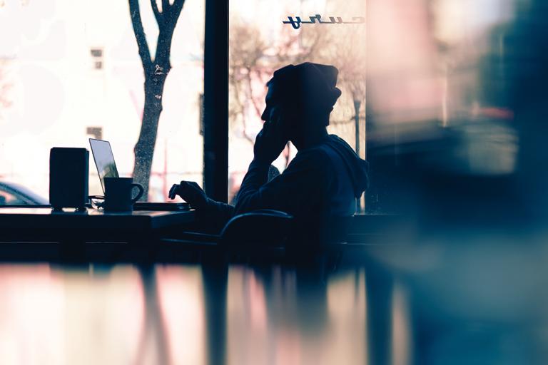 junger mann im gegenlicht arbeitet am laptop im cafe, foto: unsplash.com, hannah-wei