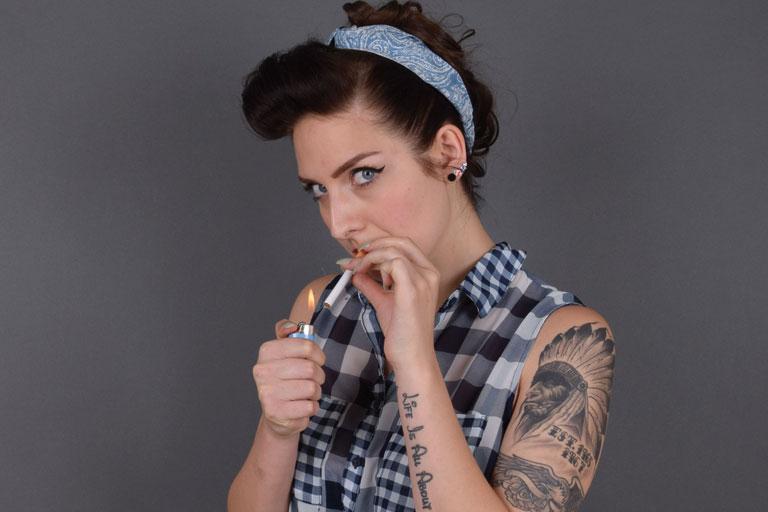 ausstellungs-projekt anders schoen - junge frau mit tattoos, rauchend, foto: paedagogisches institut