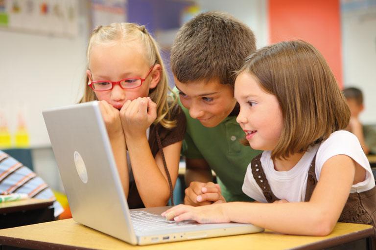 drei grundschulkinder am laptop, foto: istock, lewkmiller