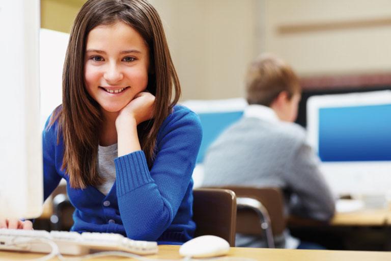 laechelndes maedchen an computer im klassenzimmer, foto: istock, globalstock