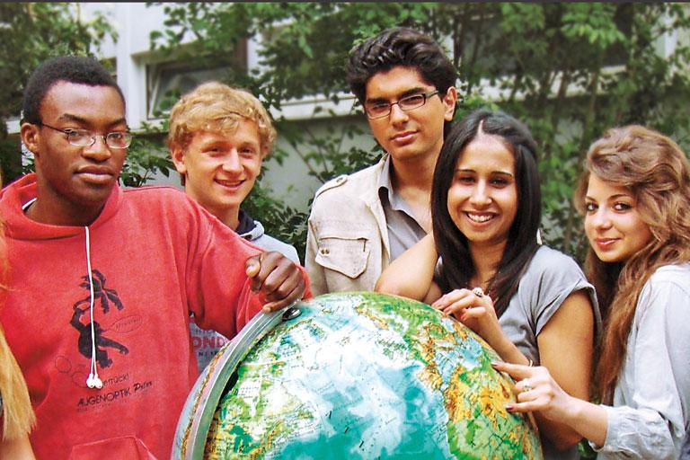 mulitikuturelle schueler_innen-gruppe versammelt sich um globus