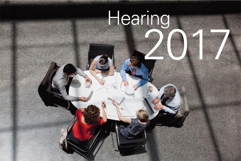 diskussionsrunde am konferenztisch – schriftzug hearing, foto: istock, tom merton
