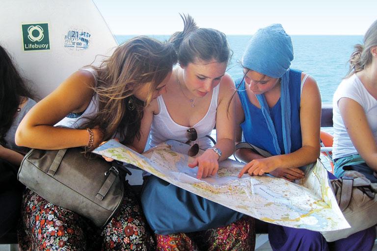 internationales ferienprogramm - drei schuelerinnen studieren landkarte, foto: paedagogisches institut