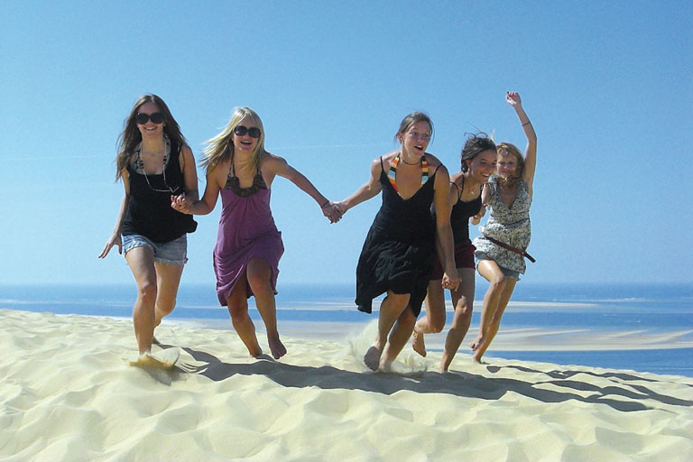 internationales ferienprogramm - fuenf junge frauen laufen hand-inhand am strand, foto: paedagogisches institut