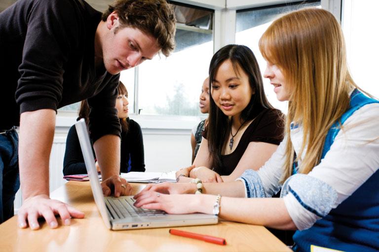 lehrer hilft studierenden am laptop, foto: istock, urbancow
