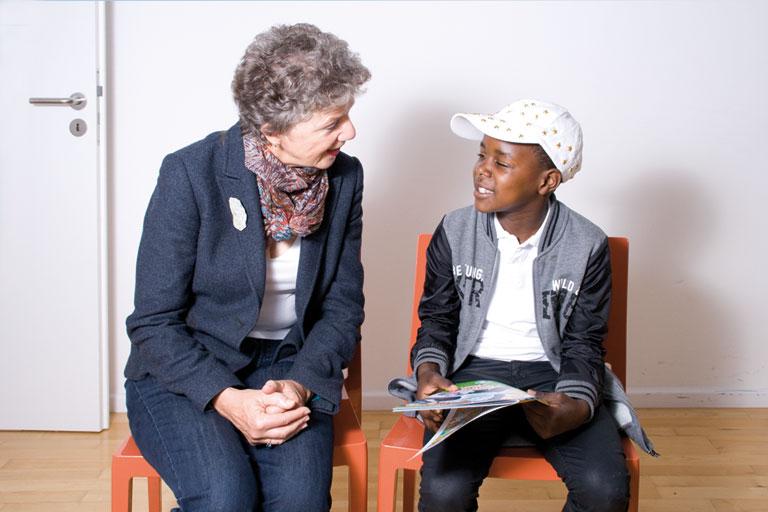 aeltere dame spricht mit dunkelhaeutigem schueler, foto: lernpaten akademie