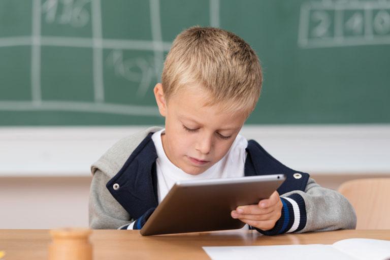 kleiner junge schaut konzentriert auf tablet-pc vor tafel, foto: fotolia, contrastwerkstatt