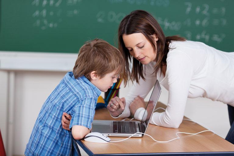 lehrerin und schueler arbeiten am laptop vor tafel, foto: fotolia, contrastwerkstatt