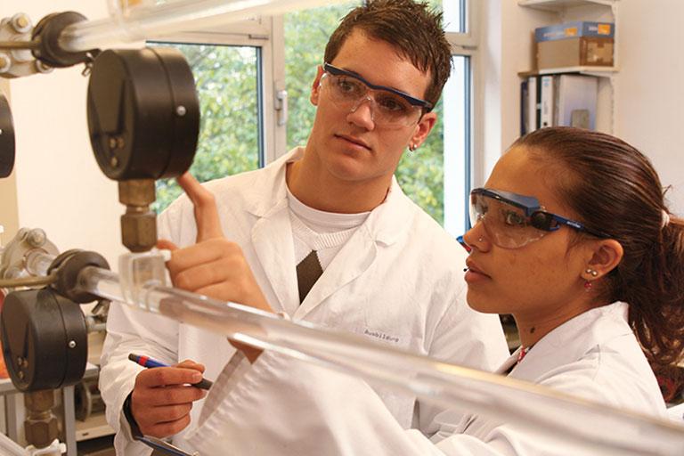 ausbilderin in einem labor zeigt dem auszubildenden, welche werte er vom manometer ablesen und in das journal eintragen muss