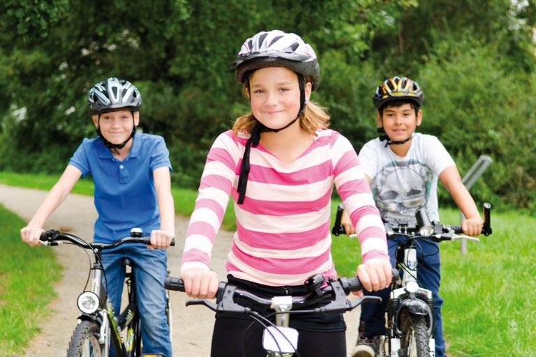 drei kinder auf dem fahrrad mit helm, foto: fotolia, racle fotodesign