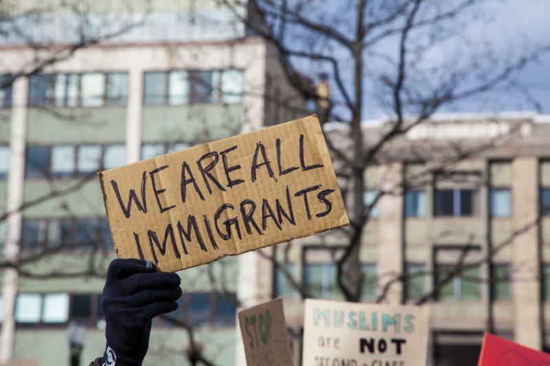 pappschild we are all immigrants vor gebaeude, foto: fotolia, jp photography