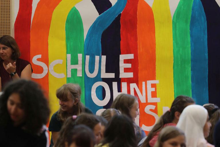 schule ohne rassismus, schulklasse mit beschriftetem regenbogen-banner auf der buehne, foto: paedagogisches institut