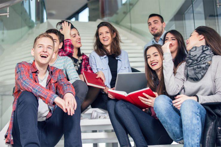 schueler_innengruppe sitzt auf der treppe im schule-gebaeude, foto: istock, ovanmandic