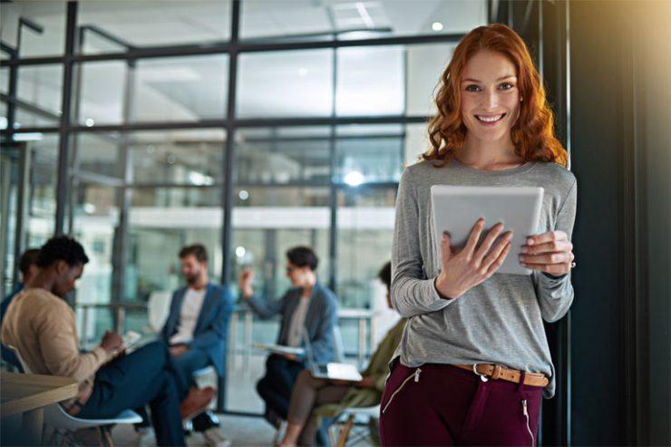 junge frau mit laptop in der hand lehnt an buerotuer, foto: istock, peopleimages