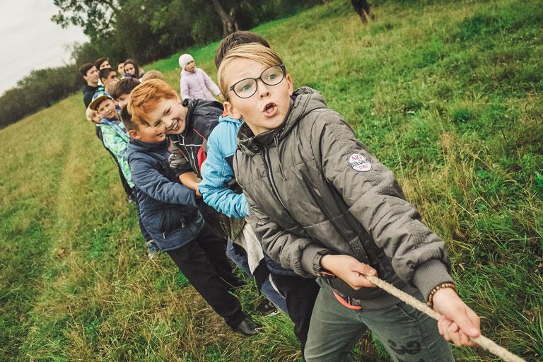 gruppe kinder beim tauziehen im gruenen, foto: unsplash.com, anna-samoylova