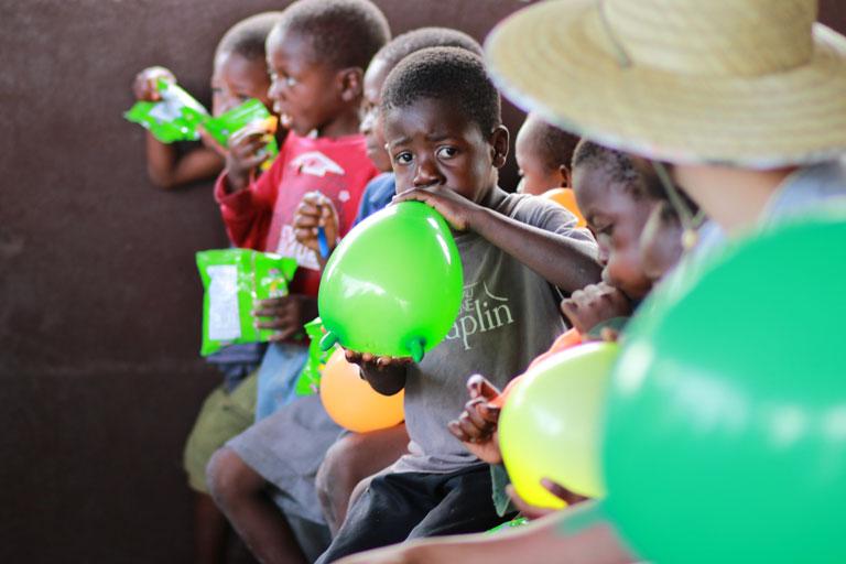 reihe dunkelhaeutiger kinder mit luftballons, foto: unsplash.com, bailey-torres