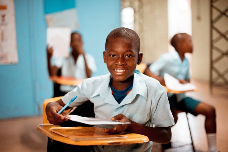 lachender, afroamerikanischer junge in schuluniform am schultisch, foto: unsplash.com, ben-white