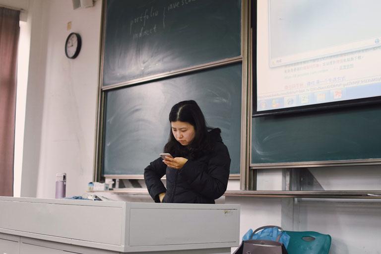 asiatische lehrerin mit handy vor tafel, foto: unsplash.com, hailang-lee