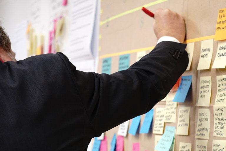 anzugtraeger macht notizen zwischen haftnotizen an der wand, nahaufnahme, foto: unsplash.com, jo-szczepanska