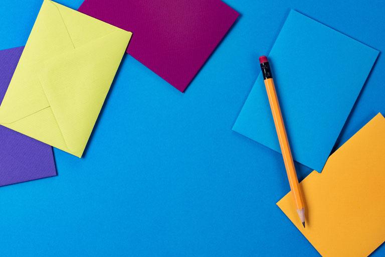 nahaufnahme farbpapier mit umschlag und stift, foto: unsplash.com, joanna-kosinska