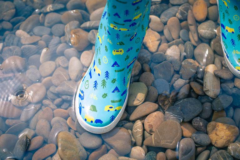 kinder-gummistiefel in kieselstein-wasser, foto: unsplash.com, markus-spiske
