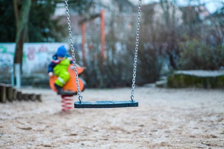 spielplatz mit schaukel im vordergrund, foto: unsplash.com, markus-spiske