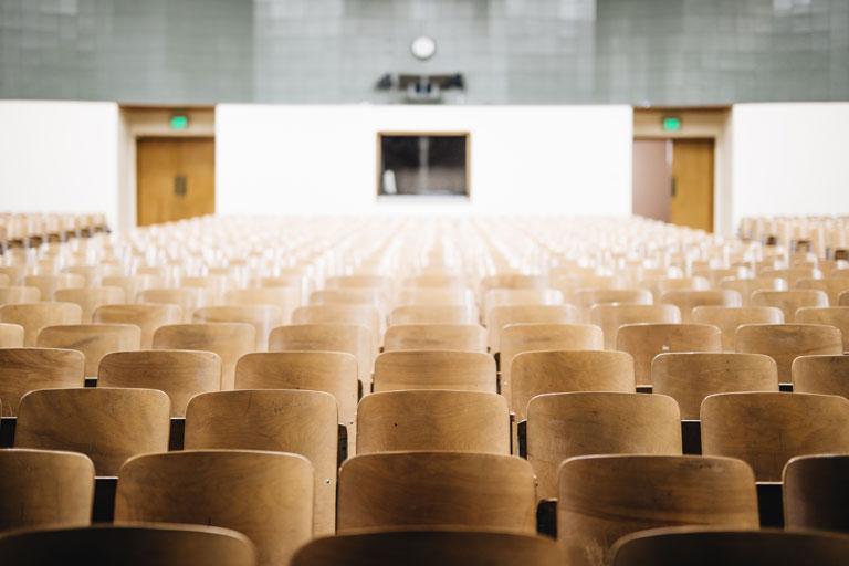 holz-stuhlreihen in einem saal, foto: unsplash.com, nathan-dumlao