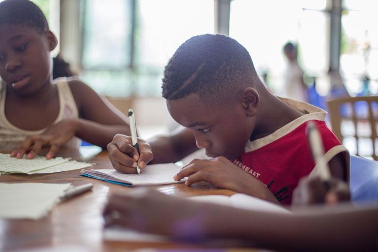 kleiner dunkelhaeutiger junge schreibt in schulklasse, foto: unsplash.com, santi-vedri