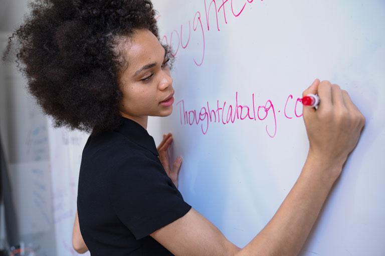 junge afroamerikanerin schreibt am flipchart, foto:unsplash.com, thought-catalog