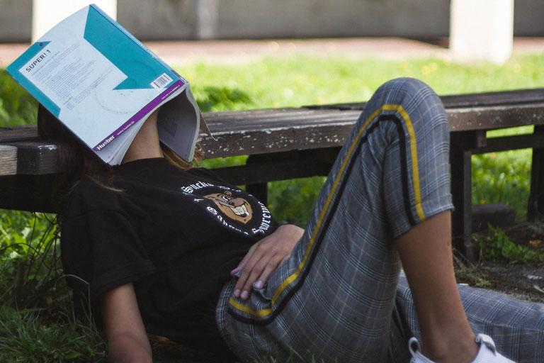 entspannung im gruenen, mit buch auf dem gesicht, foto: unsplash.com, tonny-tran