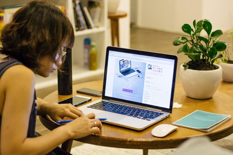 asiatin arbeitet vorm laptop am tisch sitzend, foto: unsplash.com, tran-mau-tri-tam