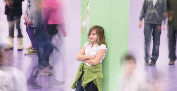 thema mobbing - maedchen steht isoliert am dem schulhof, foto: referat fuer bildung und sport
