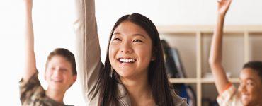 3 schueler_innen im unterricht zeigen gleichzeitig auf, foto: fotosearch