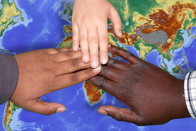 3 haende diverser ethnien ueber weltkarte, foto: capri23auto auf pixabay